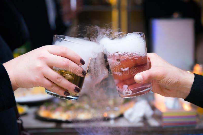 拿着干冰鸡尾酒的美好的夫妇在党 与冰蒸气的紫色鸡尾酒饮料在俱乐部,庆祝 免版税库存图片