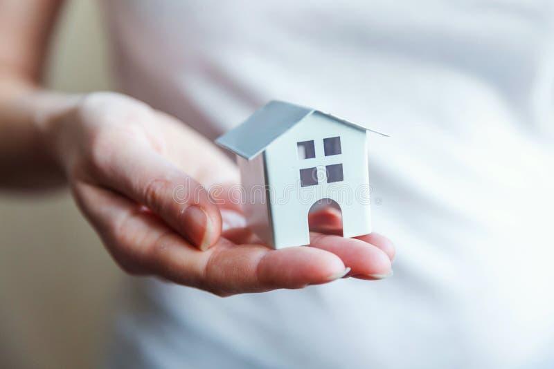 拿着微型白色玩具房子的女性妇女手 免版税库存照片