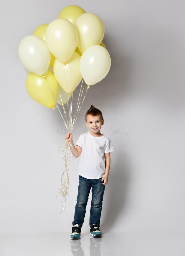 拿着很多气球的逗人喜爱的孩子 免版税图库摄影