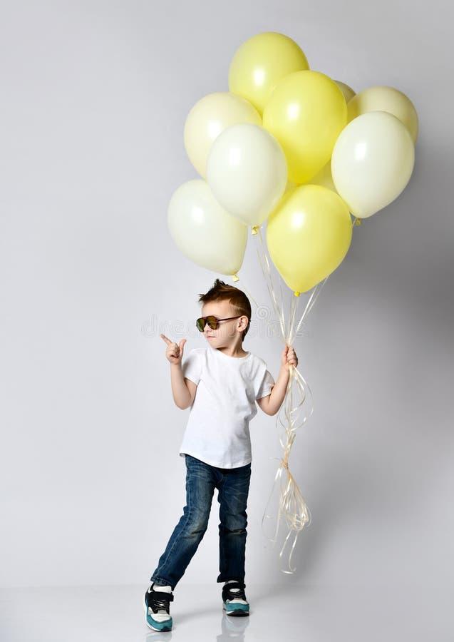 拿着很多气球的逗人喜爱的孩子 库存图片