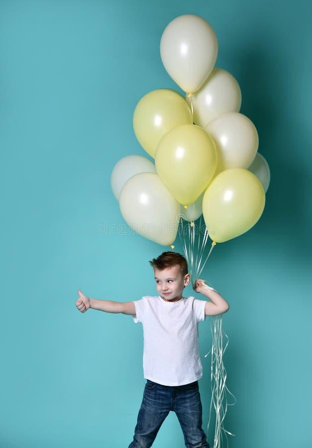 拿着很多气球的逗人喜爱的孩子 库存照片