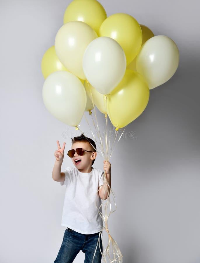 拿着很多气球的逗人喜爱的孩子 图库摄影