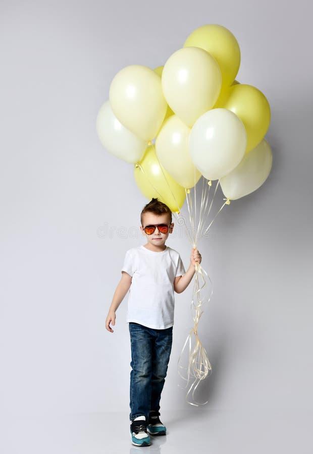 拿着很多气球的逗人喜爱的孩子 免版税库存图片