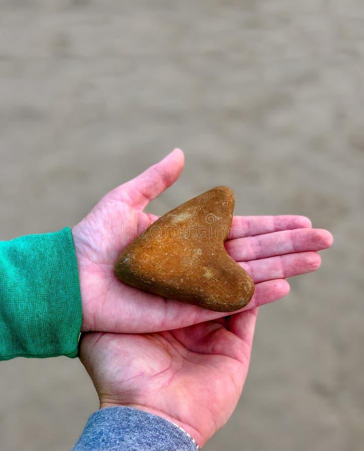 拿着心形的岩石的手反对中立背景 免版税库存图片