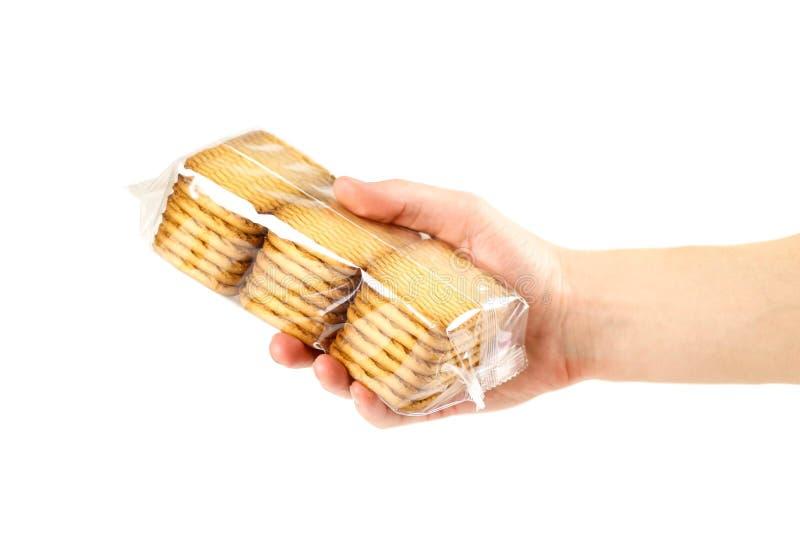 拿着在一个透明包裹的手一个金黄曲奇饼 关闭 在空白背景 免版税图库摄影