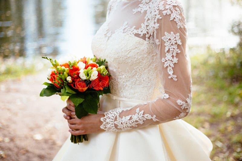 拿着在婚礼的新娘大婚礼花束 免版税图库摄影