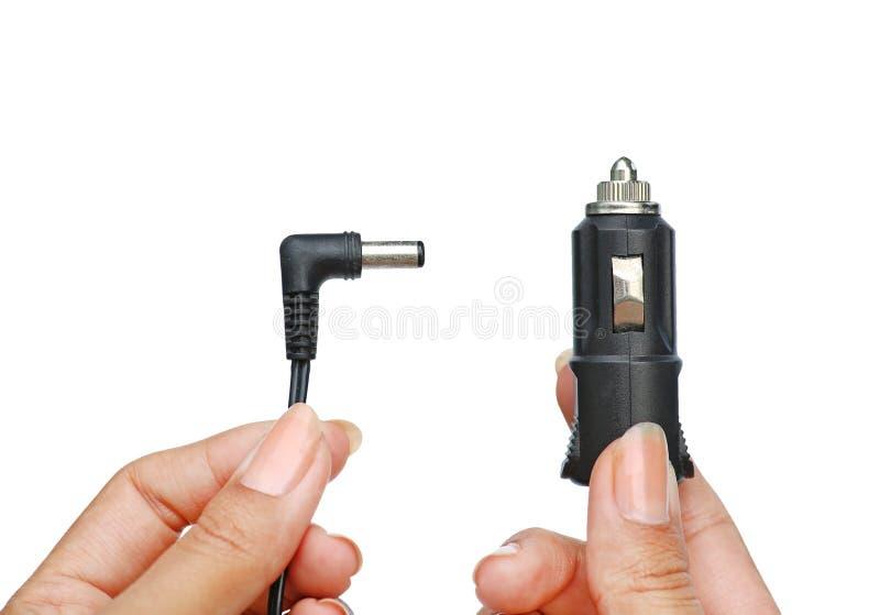 拿着在汽车的手插座插口12伏特对收费对等 背景查出的白色 库存图片