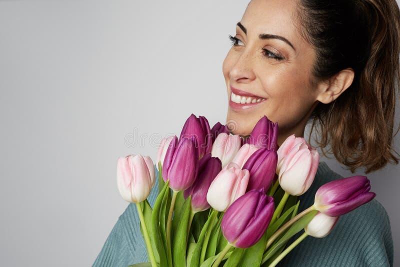 拿着在灰色背景的一微笑的年轻女人的特写镜头画象色的郁金香花束 图库摄影