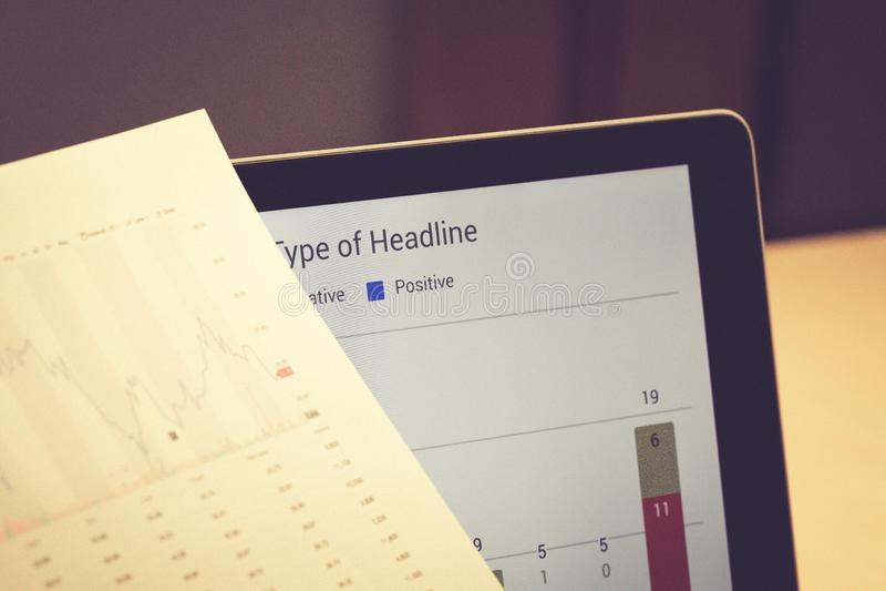 拿着在笔记本屏幕前面的商人分析文件 库存图片