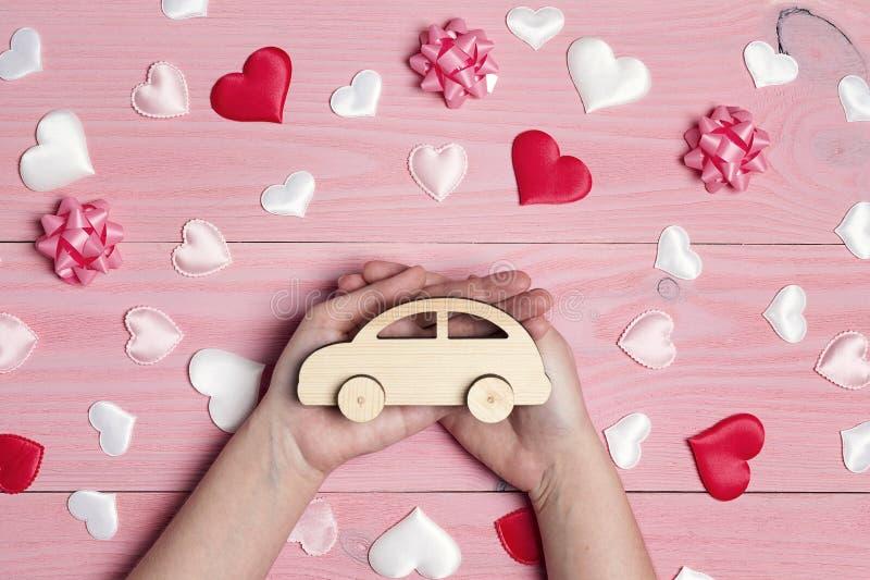 拿着在爱桃红色背景的妇女的手一辆木玩具汽车 免版税库存照片