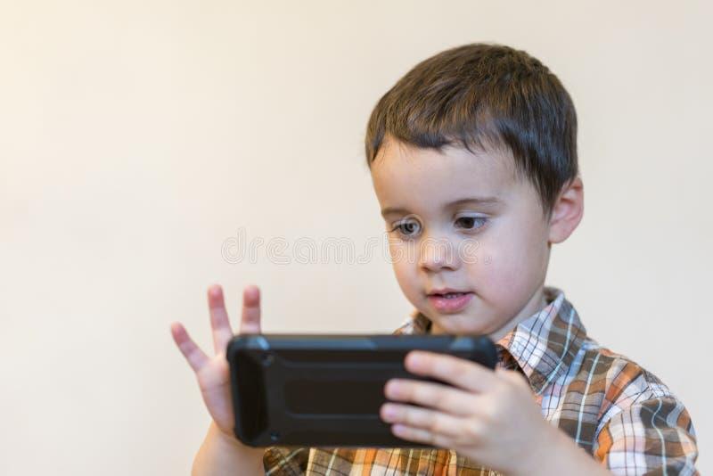 拿着在轻的背景的一个微笑的小男孩的画象手机 打在智能手机的逗人喜爱的孩子比赛 免版税库存图片