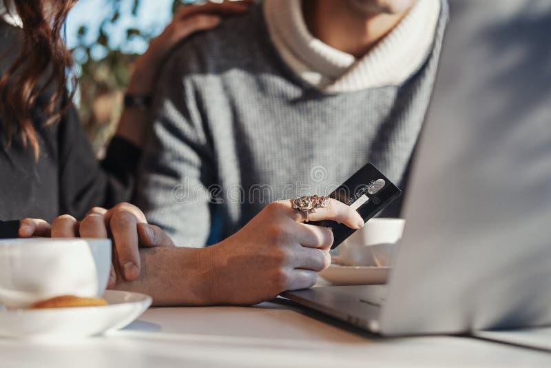拿着在膝上型计算机前面的年轻女人手信用卡 拟订dof重点现有量在线浅购物非常 库存图片