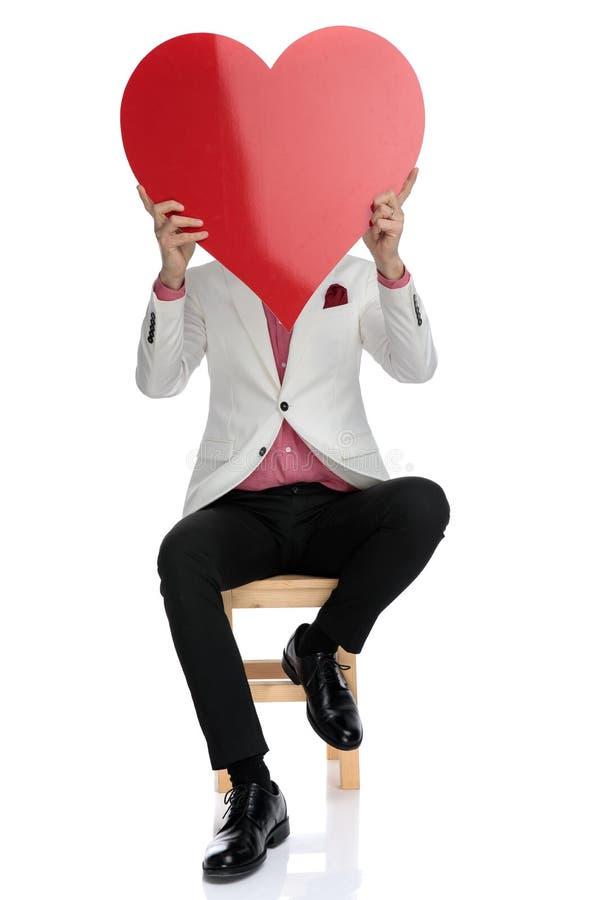 拿着在面孔的安装的时髦人士一大红心 库存图片