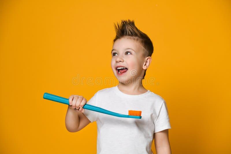 拿着在黄色背景的一个小男孩的画象一把牙刷 免版税库存照片