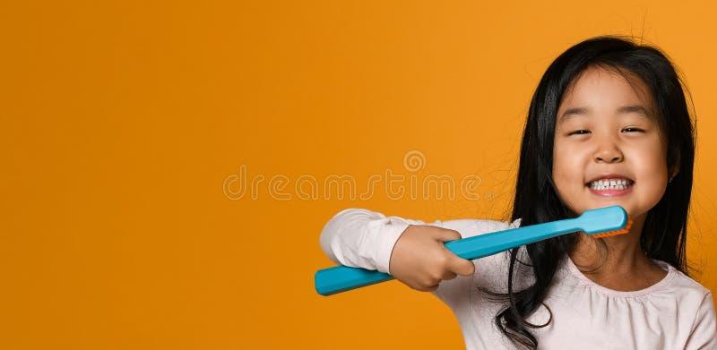 拿着在黄色背景的女孩的画象一把牙刷 免版税库存照片