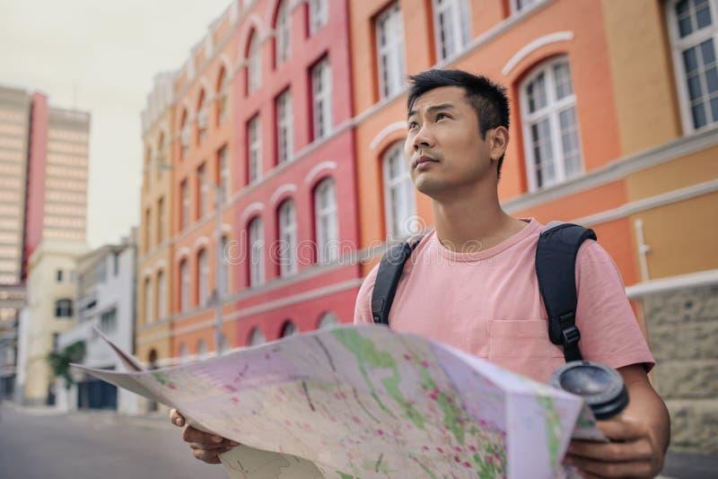 拿着地图的年轻亚裔人,当探索城市时 库存照片