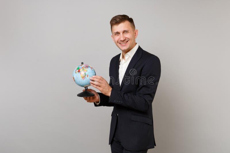 拿着地球在棕榈的经典黑衣服衬衣的可爱的年轻商人世界地球隔绝在灰色墙壁上 库存图片