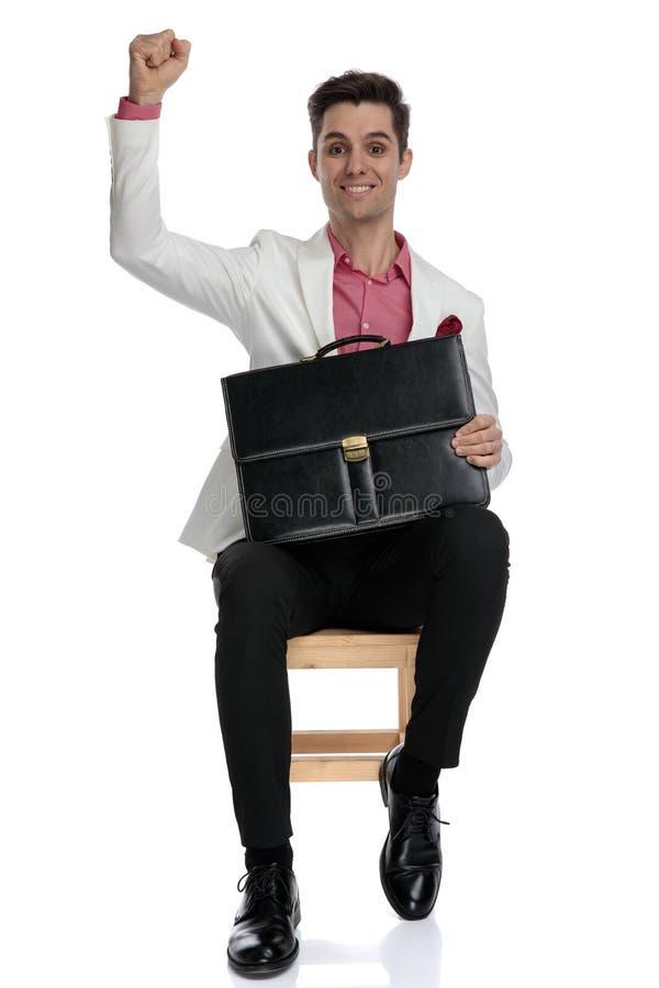 拿着公文包的安装的年轻商人庆祝成功 库存照片