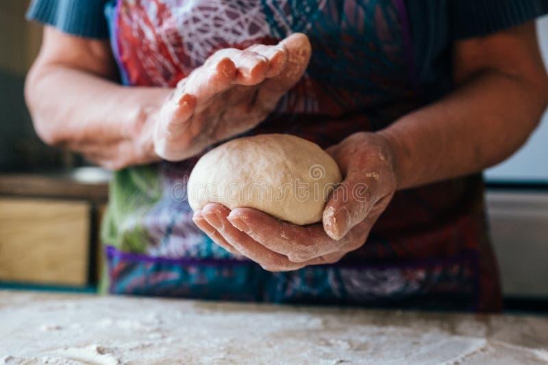拿着和揉新鲜面包面团的起皱纹的祖母手 库存图片
