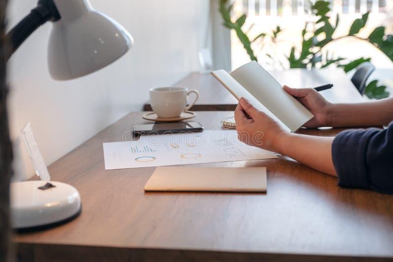拿着和打开有咖啡杯和纸的妇女一个空白的笔记本在桌上 库存照片