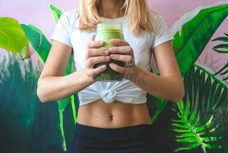 拿着杯绿色圆滑的人汁的妇女 免版税库存照片