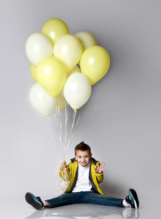 拿着束气球的孩子停留在白色背景的膝盖 免版税库存照片