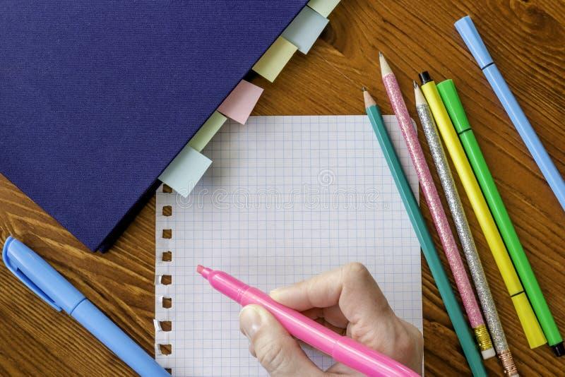 拿着桃红色轮廓色_的手,在有明显的页的笔记本旁边 库存图片