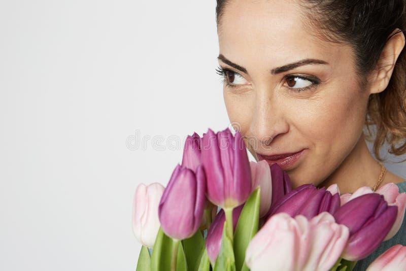 拿着桃红色郁金香花束的一快乐的少女的画象被隔绝在白色背景 免版税库存图片