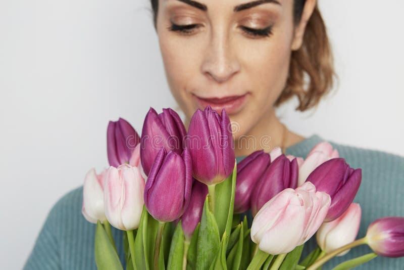拿着桃红色郁金香花束的一快乐的少女的画象被隔绝在白色背景 免版税库存照片