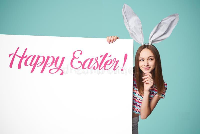拿着横幅的女孩佩带的兔宝宝耳朵 图库摄影