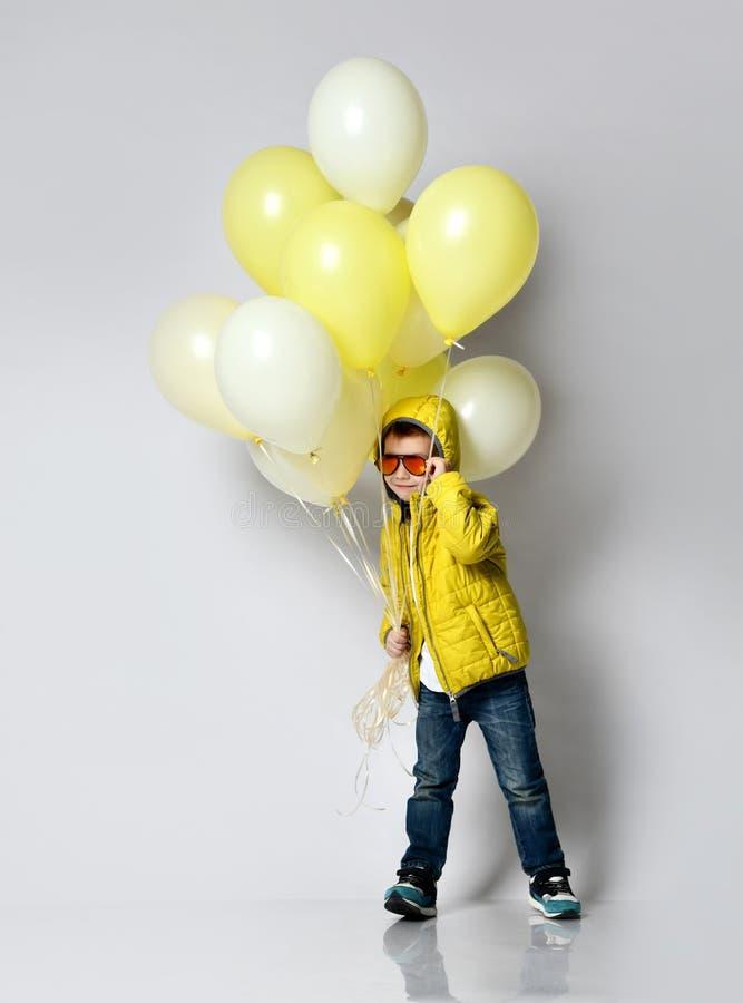 拿着气球的时髦的小男孩被隔绝在白色 免版税库存照片