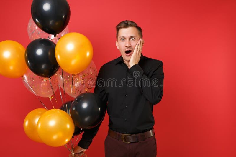 拿着气球的黑经典衬衣的震惊年轻人,保留在明亮的红色背景隔绝的面颊的手 库存图片