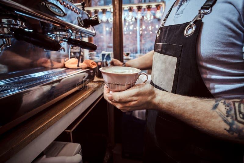 拿着有一杯芳香热奶咖啡的Barista一个杯子在咖啡馆 免版税库存照片