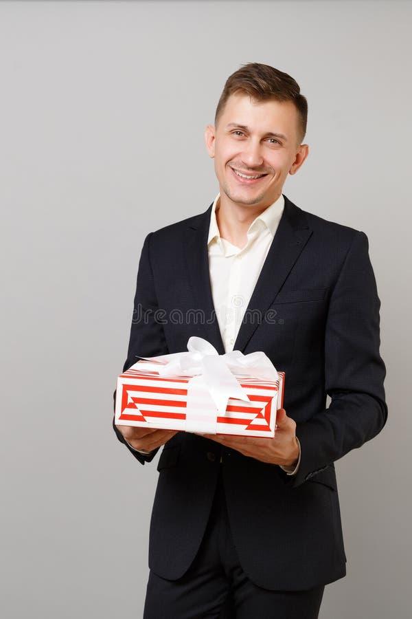 拿着有礼物丝带的衣服的宜人的年轻商人红色镶边当前箱子隔绝在灰色背景 免版税库存图片