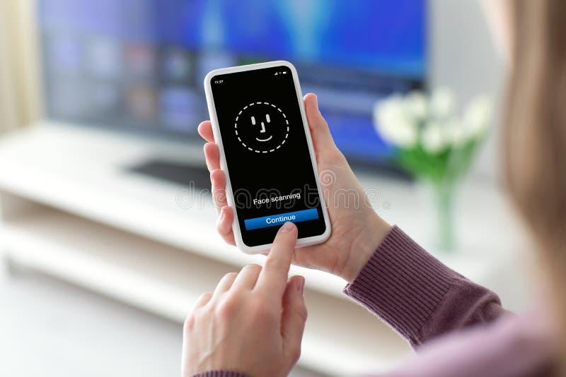 拿着有面孔ID扫描的女性手电话在屏幕上 库存照片