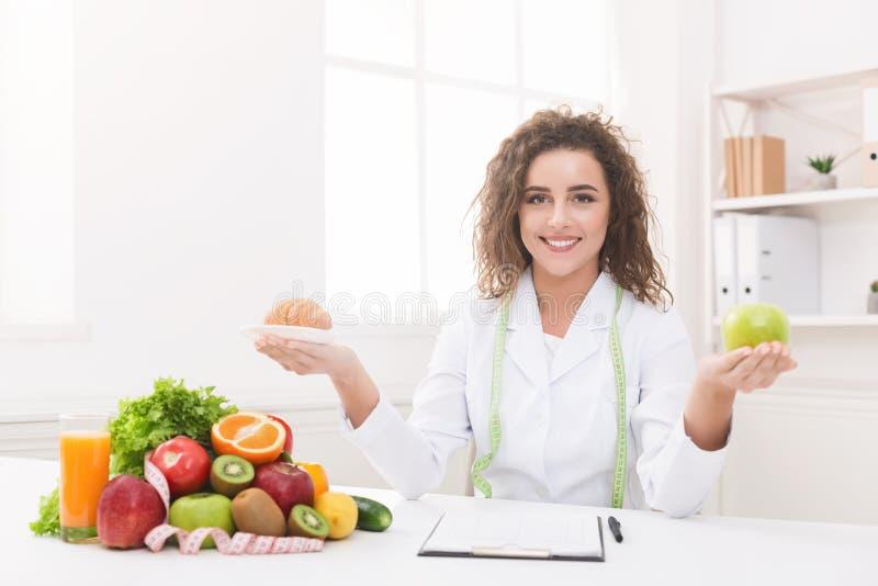 拿着果子和新月形面包在手上的妇女营养师 图库摄影