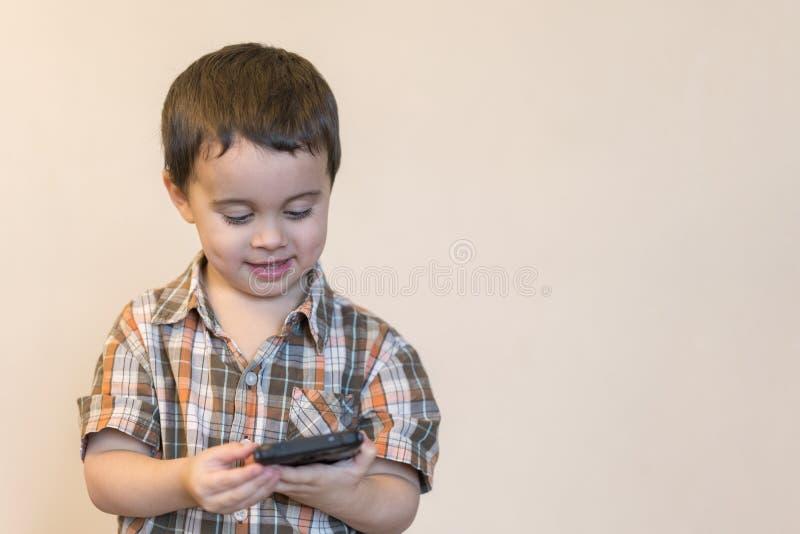 拿着手机的一个微笑的小男孩的画象被隔绝在轻的背景 打在智能手机的逗人喜爱的孩子比赛 复制 库存照片