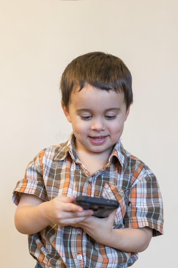 拿着手机的一个微笑的小男孩的画象被隔绝在轻的背景 打在智能手机的逗人喜爱的孩子比赛 库存照片