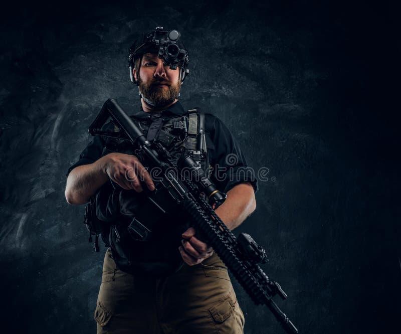 拿着攻击步枪的有胡子的特种部队战士或私有军事承包商和观察周围  免版税库存图片