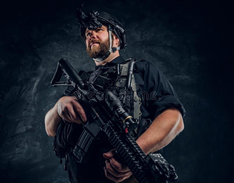 拿着攻击步枪的有胡子的特种部队战士或私有军事承包商和观察周围  库存图片