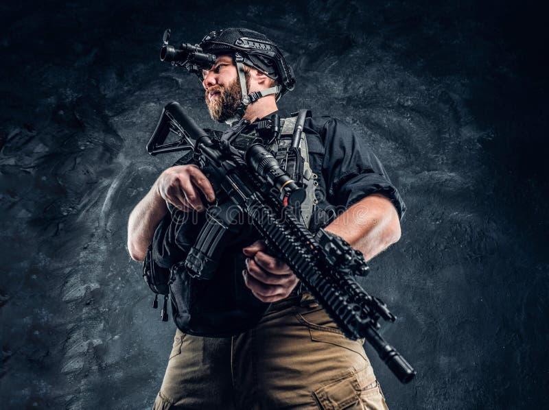拿着攻击步枪的有胡子的特种部队战士或私有军事承包商和观察周围  免版税库存照片