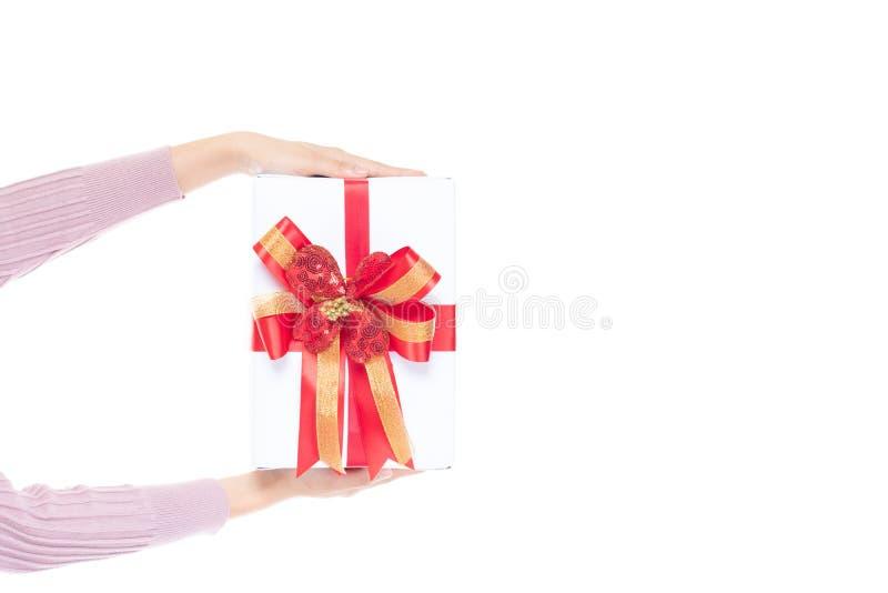 拿着礼物盒的女性手包裹与在与拷贝空间的白色背景隔绝的红色丝带 妇女手藏品礼物盒 免版税图库摄影