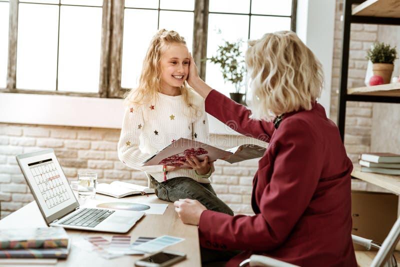 拿着秀丽杂志一会儿母亲的微笑的快乐的孩子接触她的面孔 免版税图库摄影