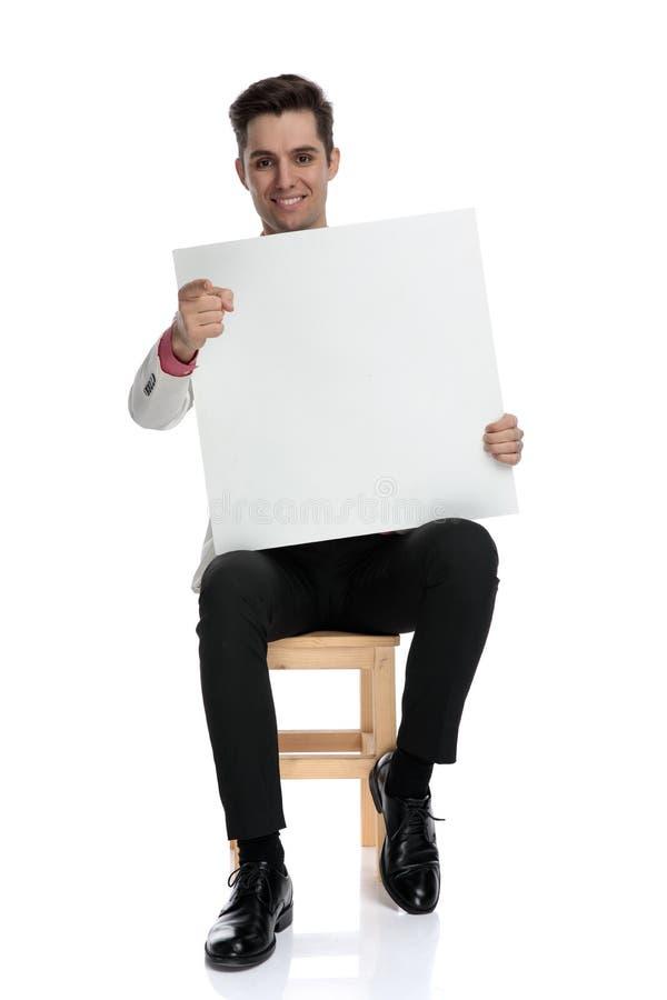 拿着空白的委员会的安装的典雅的人指向手指 免版税库存图片