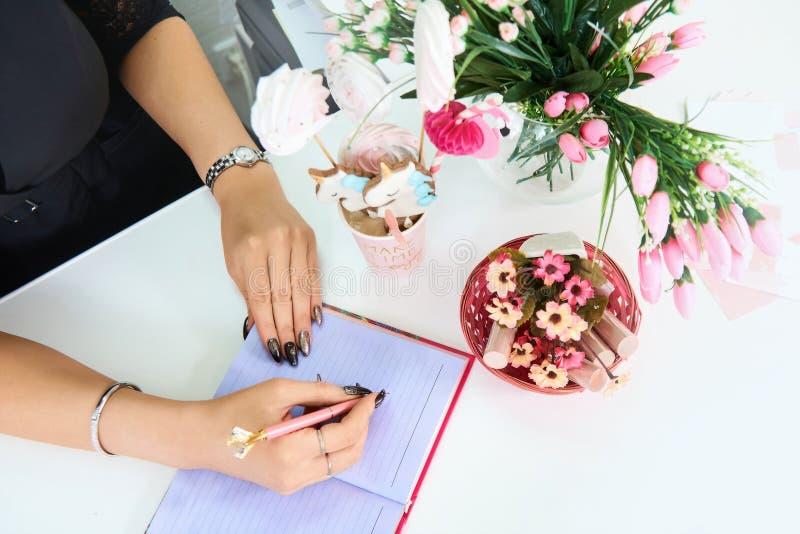 拿着笔的手欧洲女孩和写在一个空的笔记本 附近花和糖果 库存照片