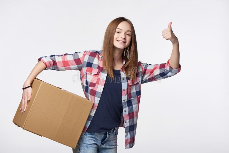 拿着纸板箱的愉快的女孩打手势赞许 库存照片