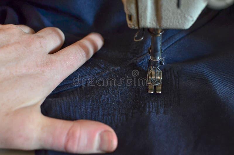 拿着织品的男性手,当缝合在一台缝纫机时的裤子 缝,针在蓝色牛仔裤的一个孔或编织sweatpants 免版税库存图片