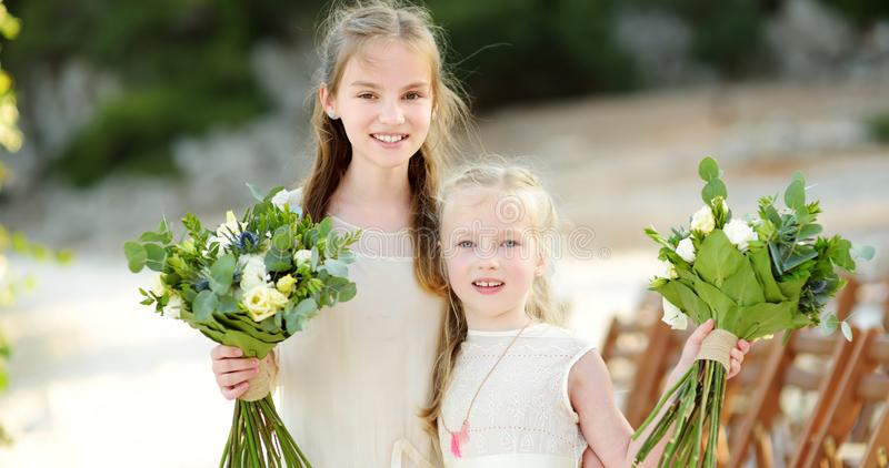 拿着美丽的花花束的两个可爱的年轻女傧相在婚姻的cemerony户外以后 免版税库存图片
