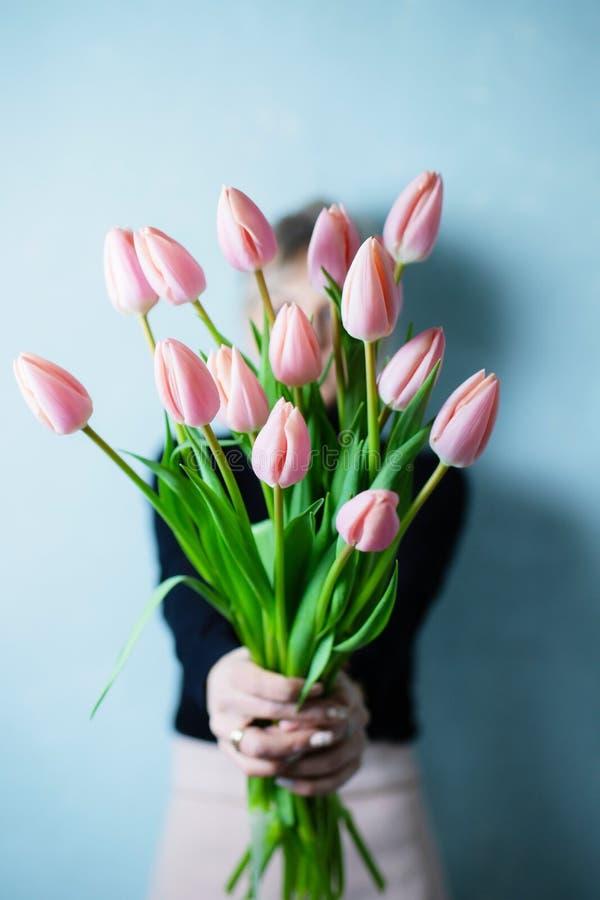 拿着美好的束郁金香的少妇在她的手上 免版税库存照片