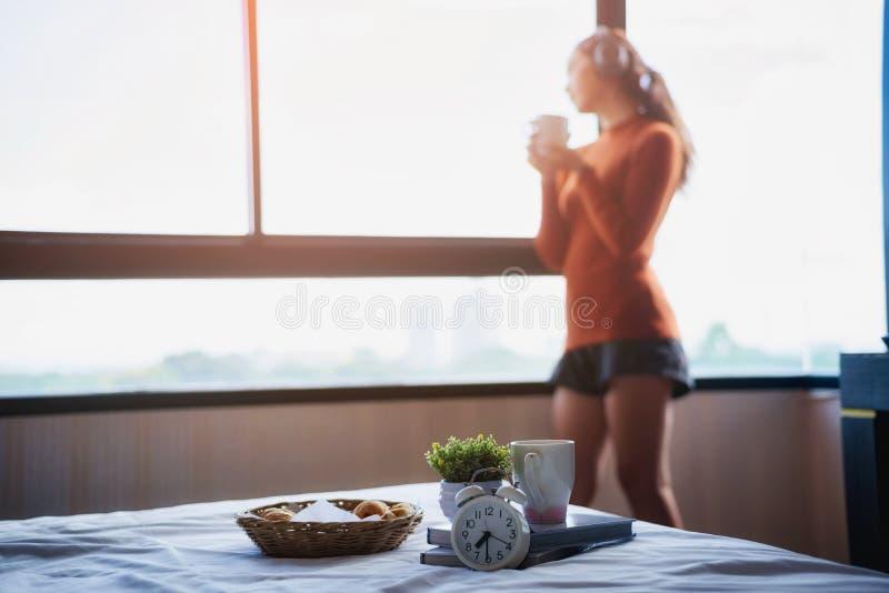 拿着热的杯子咖啡和使用耳机的年轻美女手听到音乐为放松在早晨阳光下 库存照片